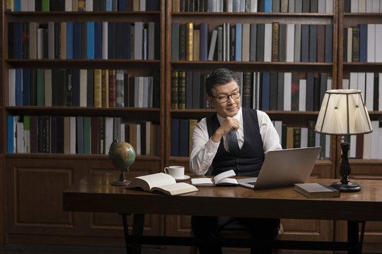 Senior businessman using laptop in study