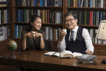 Cheerful mature couple talking and drinking tea in study