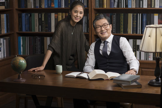 Cheerful mature couple reading book in study