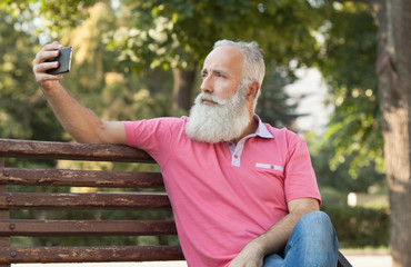 Old active bearded man taking selfie with mobile phone in park