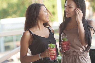 Gay female couple have postive expressions, sit close to each other at cafeteria, smile joyfully, enjoy tasty desserts in outdoor cafeteria. Multiethnic lesbians talk to each other. Love concept.
