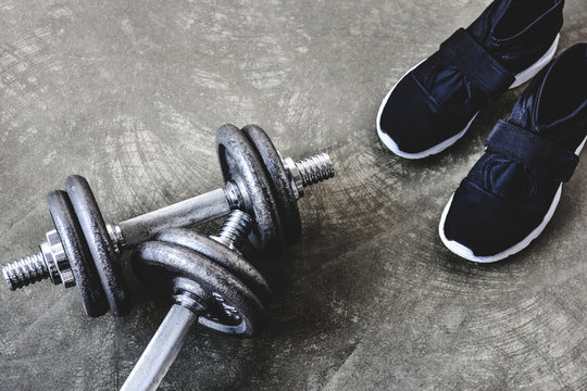 close-up shot of adjustable dumbbells with sneakers on concrete surface