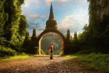 Lady hold red umbrellas with arch at Khao Na Nai Luang Dharma Park in Surat Thani Thailand Wall mural