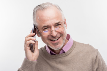Happy man. Image without face retouching with handsome bearded senior man feeling happy while having phone conversation