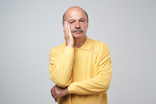 Closeup portrait of mature depressed man in yellow shirt really sad, deep in thought, looking up asking question why me isolated on gray background. Human face expressions, emotion, feeling, reaction