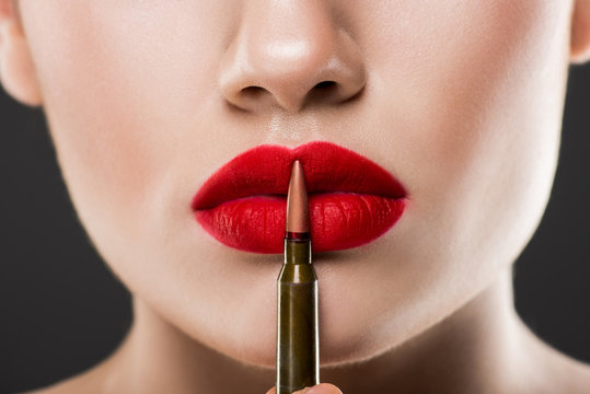partial view of young woman holding bullet near red lips, isolated on grey