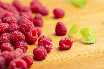 Fresh raspberry with mint on wooden background