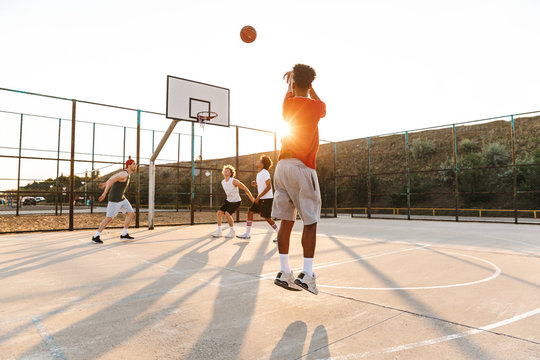 Group of young cheerful multiethnic men basketball