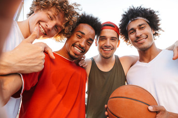 Young beautiful guys smiling and taking selfie, while playing basketball at playground outdoor during summer sunny day