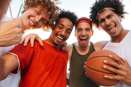 Photo closeup of handsome players men smiling and taking selfie, while playing basketball at playground outdoor during summer sunny day