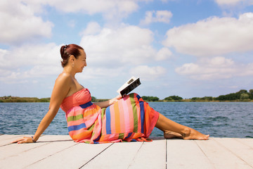 Smiling woman reading book on pier at the beach.