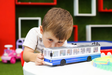 Cute boy playing with trolley car. Developing toys.