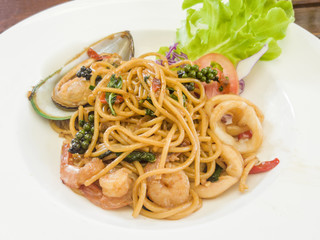 Spaghetti with spicy mixed seafood on a white plate