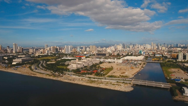 Aerial view skyline of Manila city, Makati. Fly over city with skyscrapers and buildings. Aerial skyline of Manila. Modern city by sea, highway, cars, skyscrapers, shopping malls. Travel concept.