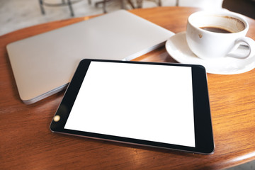 Top view mockup image of a black tablet pc with blank desktop white screen with laptop and coffee cup on wooden table