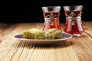 Turkish Dessert fıstık ezmesi baklava with pistachio on wooden table.
