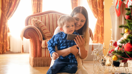 Portrait of smiling cheerful toddler boy sitting with mother under Christmas tree and watching video on smart phone