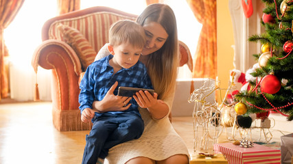 Little toddler boy watching cartoons with mother on smartphone next to Christmas tree