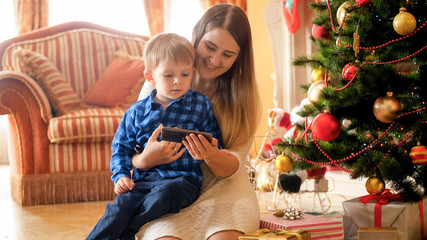 Portrait of smiling young mother embracing her little boy and watching video on smartphone next to Christmas tree