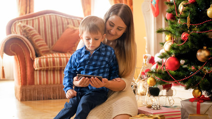 Portrait of young mother with toddler boy relaxing on Christmas morning and watching video on mobile phone