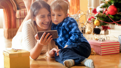 Laughing young family with little son lying on floor on Christmas morning and watching video on smart phone