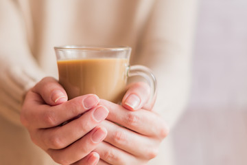 woman in beige sweater holding a glass cup with coffee to get warm.