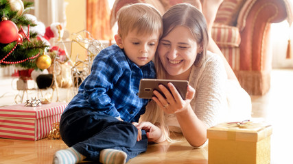 Portrait of adorable toddler boy lying with mother on Christmas morning and watching cartoons