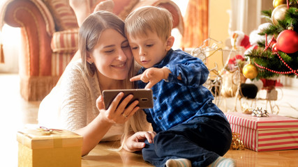 Adorable toddler boy watching video on smartphone with mother lying on floor