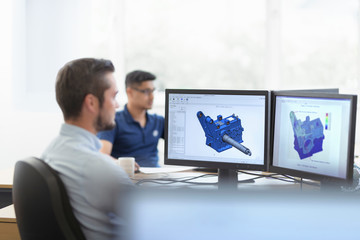 Engineers designing gearboxes using computer aided design (CAD) software in gearbox factory