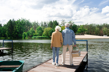 Romantic date. Stylish elderly wife and husband feeling extremely excited while having romantic date near river