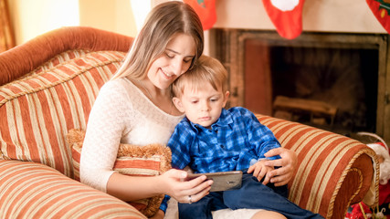 Portrait of beautiful smiling young woman resting in armchair with her little boy and watching cartoons