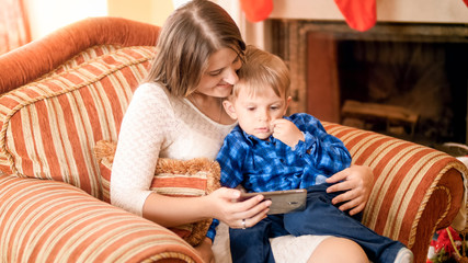 Cute little boy sitting on others lap in armchair and watching cartoons on smartphone
