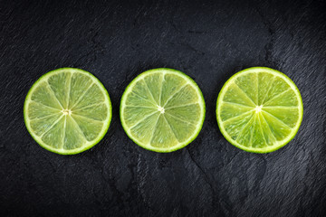 An overhead photo of three lime slices on a black background
