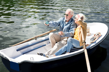 Posing for photo. Beaming elderly lady posing for photo with her bearded stylish husband while sitting in boat