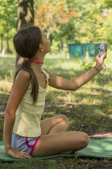 Little cute girl holding camera in hand and take a picture with selfie shot in park. beautiful eight-year-old girl in the park doing selfie. vertical photo.