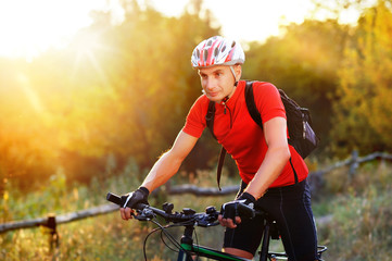 Closeup picture of a cyclist in summer sun beams