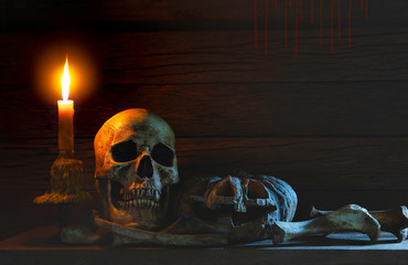 Still life style ;Skulls of bones with candle flame, Pumpkin at night on back background.Halloween day concept.