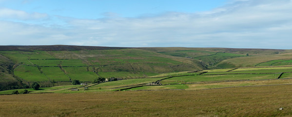 wide panoramic view of yorkshire dales landscape with fields and farmhouses enclosed by stone walls with open moorland above with blue sky and clouds