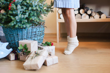 Little hild girl is decorating Christmas tree with ornaments. Kid in woolen knitted socks stands on tiptoes on warm floor with heating mat at home. Presents, gifts are under fir tree in blue basket.