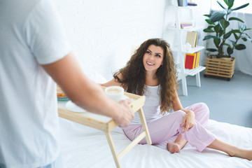 cropped shot of man holding tray with breakfast while smiling girlfriend sitting in bed