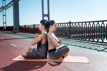 Calm inhale. Attractive confident woman and man sitting on mat board and meditating