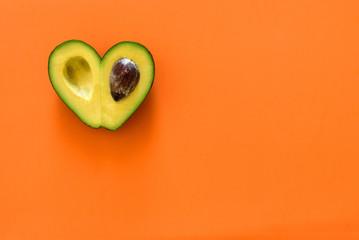Heart-shaped avocado on orange background