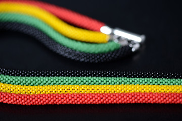 Fragment of a beaded necklace in Jamaican style on a dark background close up