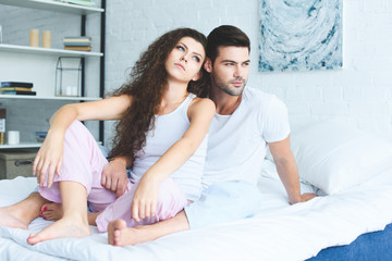 thoughtful young couple in pajamas sitting together on bed and looking away