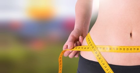 Woman measuring weight with measuring tape on waist in Summer