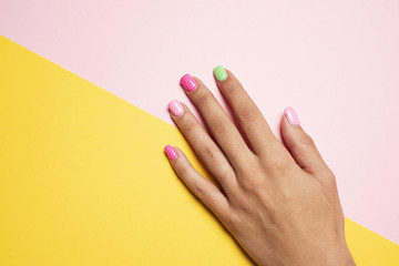 woman hand with her nails painted pink and green