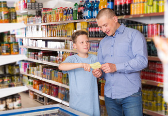 Father doing shopping with boy looking at shopping list