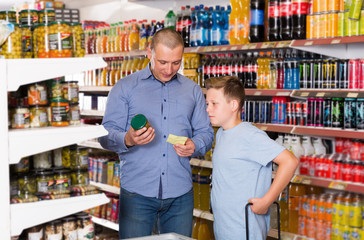 Positive father and son making purchases together with shopping list