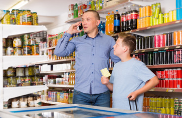 Man talking on phone and looking at shopping list
