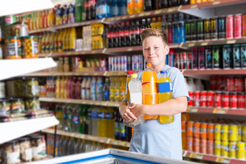 boy holding a lot of products after shopping